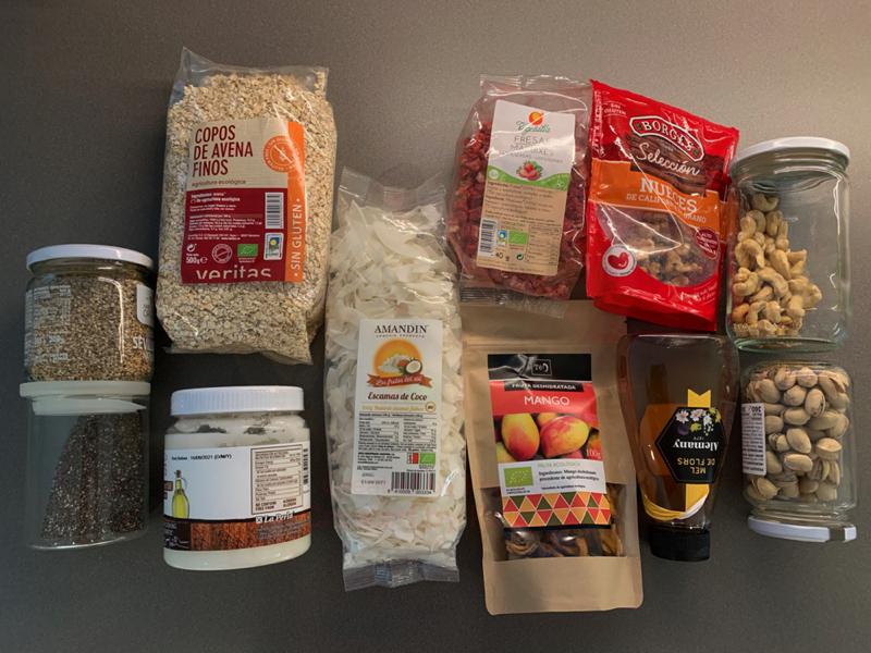 Ingredientes para hacer una receta de granola saludable con avena, fruta, frutos secos, aceite de coco, semillas y miel.